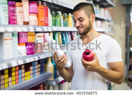 Smiling young handsome man selecting shampoo in supermarket