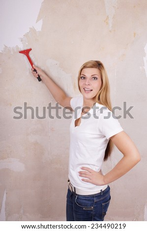 smiling young handywoman removing old wallpaper with scraper tool - stock photo