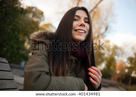 Smiling young hipster girl in grey park coat and marsala scarf. Funny model with pug nose and friendly or happy facial expression - stock photo