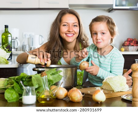 Smiling young housewife with little daughter cooking at home kitchen - stock photo