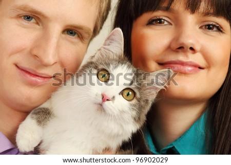 Smiling young husband and wife hold surprised cat; focus on cat - stock photo