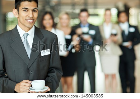 smiling young indian businessman having coffee break during seminar - stock photo