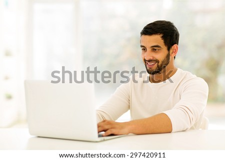 smiling young indian man using laptop at home - stock photo