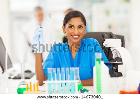 smiling young indian scientist portrait in lab - stock photo