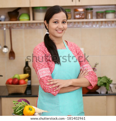 Smiling young Indian woman in her kitchen  - stock photo
