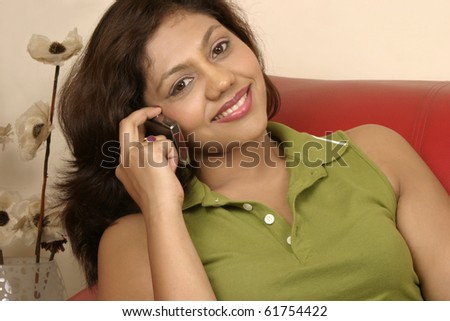smiling young Indian woman talking on mobile phone - stock photo