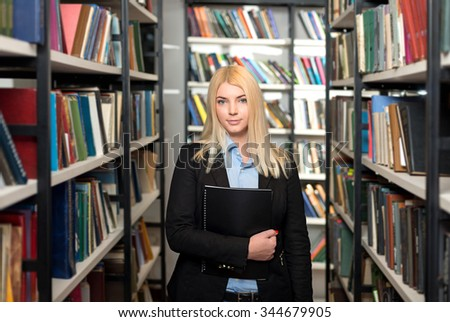 smiling young lady with loose long blonde hair standing and holding a pile books between book shelves in the library, looking in front of her, side view, a concept of studying