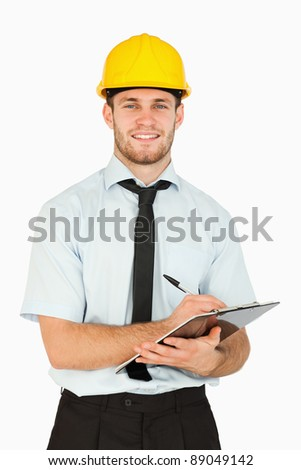 Smiling young lead worker taking notes on his clipboard against a white background - stock photo