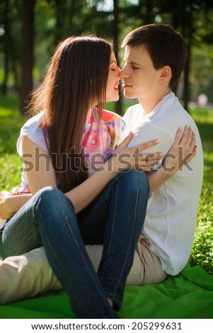smiling young lovers out in the park lying on the grass  - stock photo