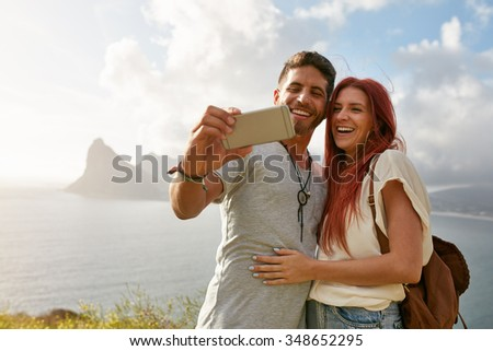 Smiling young loving couple taking self portrait outdoors in summer. Young man with his girlfriend taking selfie with mobile phone. - stock photo