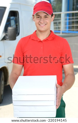 Smiling young male delivery courier man in front of cargo van delivering pizza - stock photo