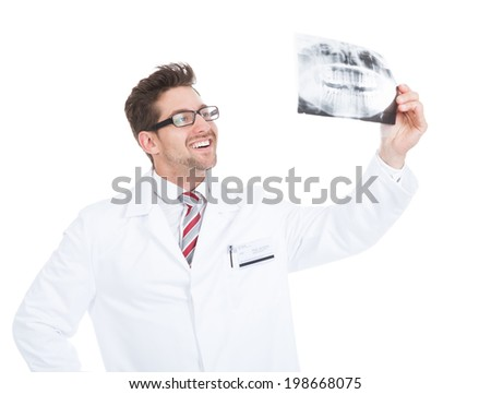 Smiling young male doctor examining dental x-ray over white background - stock photo