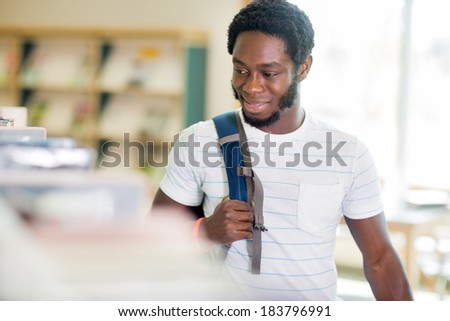 Smiling young male student carrying backpack while looking at books in bookstore - stock photo