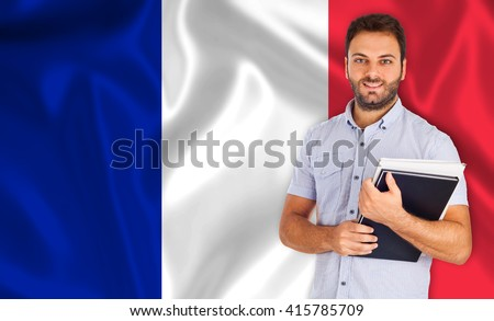 Smiling young male student over French flag