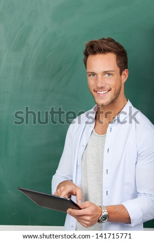 Smiling young male student with tablet pc against green chalkboard