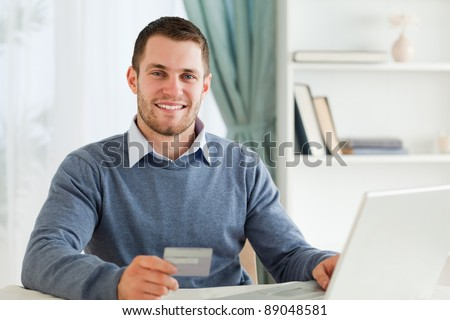 Smiling young male with credit card at his laptop - stock photo