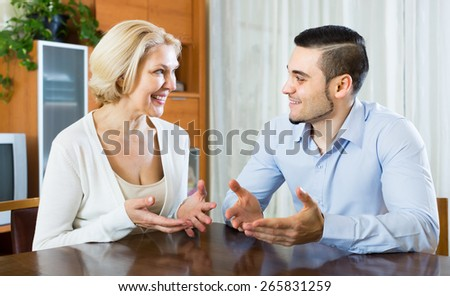 Smiling young man and elderly woman having pleasant conversation indoor