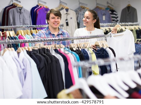 Smiling young man and woman choosing clothing at the store