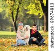 Smiling young man and woman hugging a labrador retreiver dog out in the park - stock photo
