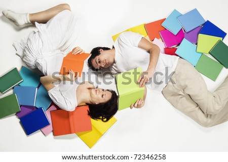 Smiling young man and woman lying on floor with colorful books and reading, looking at books, isolated on white background. - stock photo