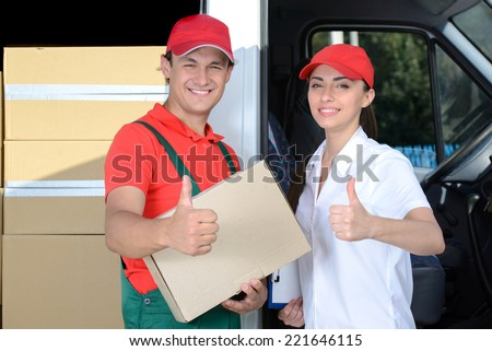 Smiling young man and woman postal delivery courier man before cargo van cargo delivery - stock photo
