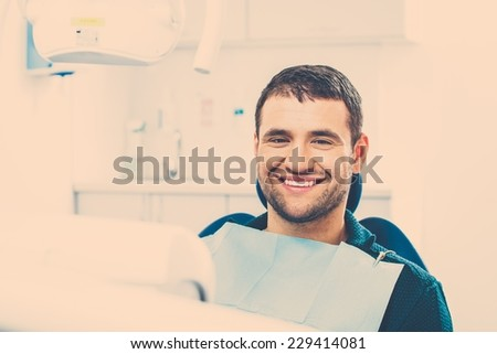 Smiling young man at dentist's surgery - stock photo