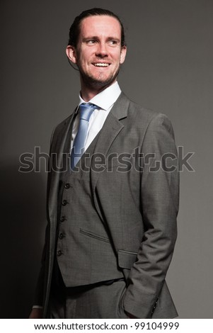 Smiling young man brown long hair with expressive face wearing grey suit and blue tie. Isolated on grey background.