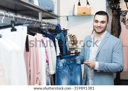 Smiling young man buying clothes for his girlfriend at boutique
