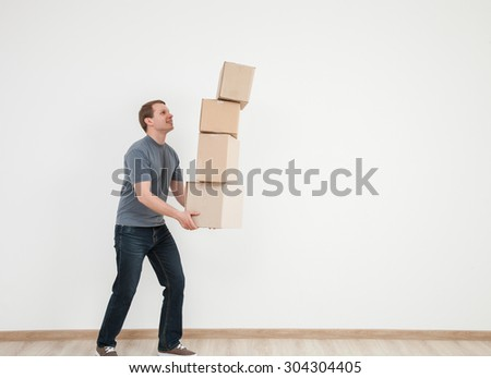 Smiling young man carrying many cardboard boxes, white background - stock photo