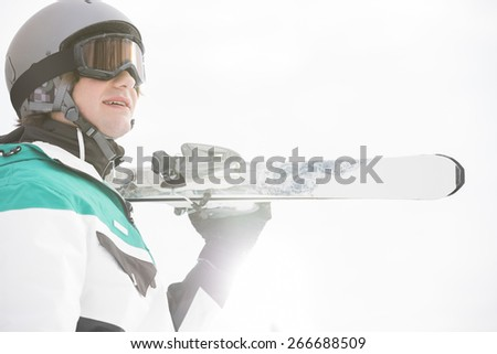 Smiling young man carrying skis against clear sky - stock photo