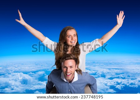 Smiling young man carrying woman against blue sky over clouds at high altitude - stock photo