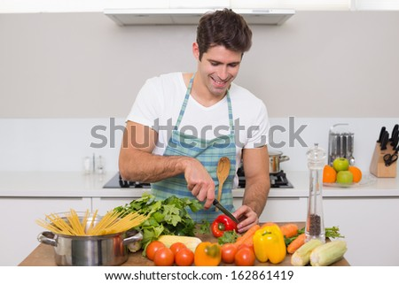 Smiling young man chopping vegetables in the kitchen at home - stock photo