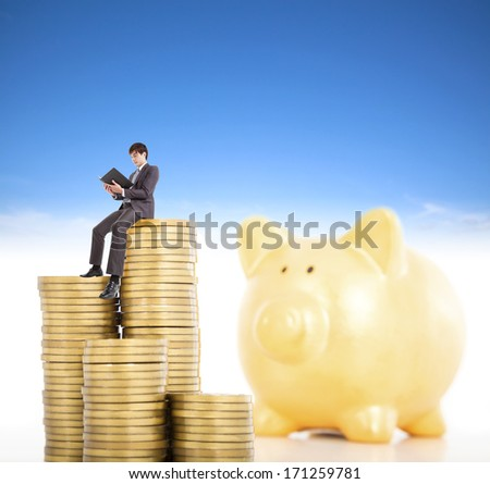 smiling young man counting coin in poggy bank  - stock photo
