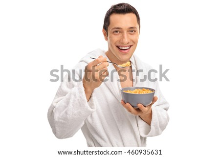 Smiling young man eating cereal from a bowl isolated on white background