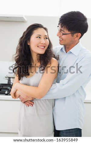 Smiling young man embracing woman from behind in the kitchen at home - stock photo