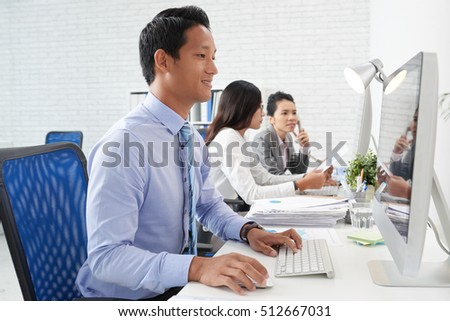 Smiling young man enjoying working in office