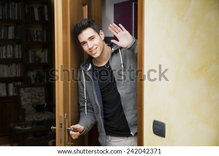 Smiling young man getting out of door waving at the camera with a friendly cheerful smile as he peers around the edge of a wooden door - stock photo
