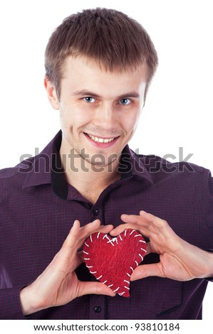 smiling young man holding a heart on a white background - stock photo
