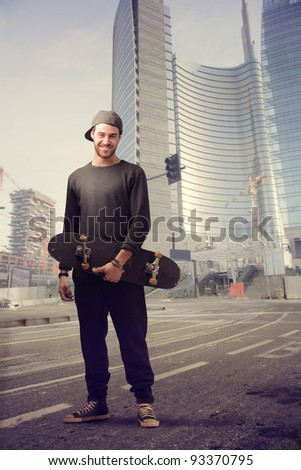 Smiling young man holding a skateboard on a city street - stock photo