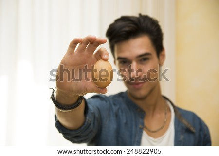 Smiling young man holding an egg in his hand, showing it to the camera - stock photo
