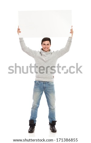 Smiling young man holding banner over his head. Full length studio shot isolated on white.