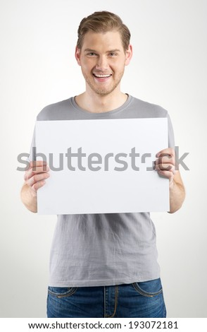 Smiling young man holding blank sign in hands