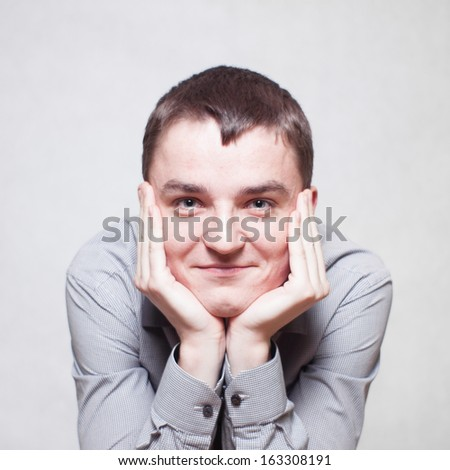 Smiling young man holding his head - stock photo