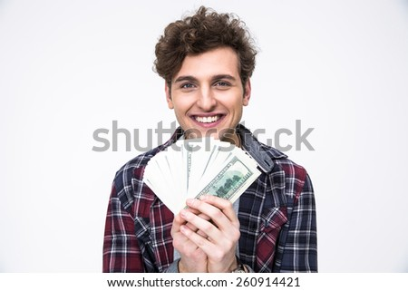 Smiling young man holding money over gray background - stock photo