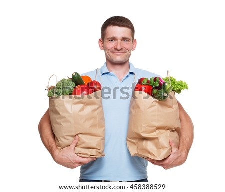 Smiling young man holding shopping bags full of groceries isolated at white background. Healthy food shopping. Paper package with vegetables and fruits, happy male buyer came from market - stock photo