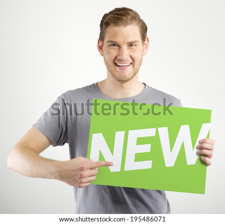 Smiling young man holding sign in hands - stock photo