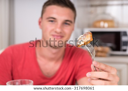 Smiling Young Man Holding Up Fork with Food Towards Camera While Sitting at Kitchen Dining Table During Dinner Meal - stock photo