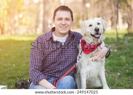 Smiling young man hugging a dog - stock photo