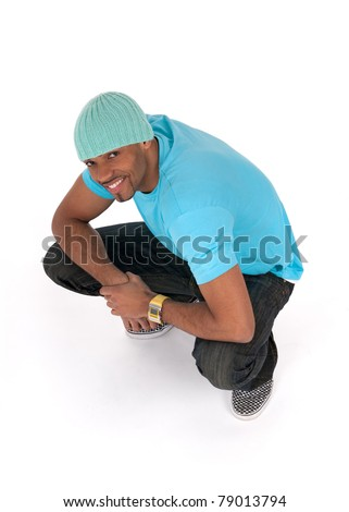 Smiling young man in a blue t-shirt squatting. Isolated on white background.