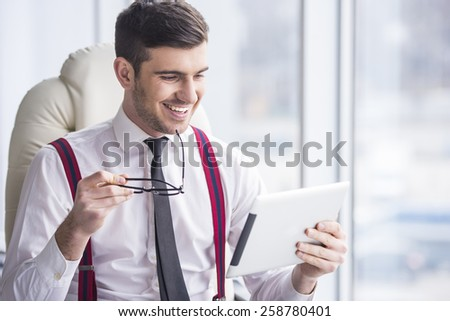 Smiling young man in a suit is holding a tablet before. - stock photo